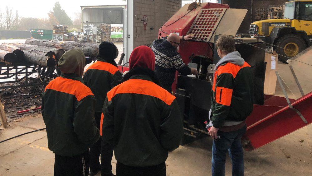 Dominik Sträßer, Mitarbeiter der GESA, zeigt Schülern Methoden zur Holzverarbeitung